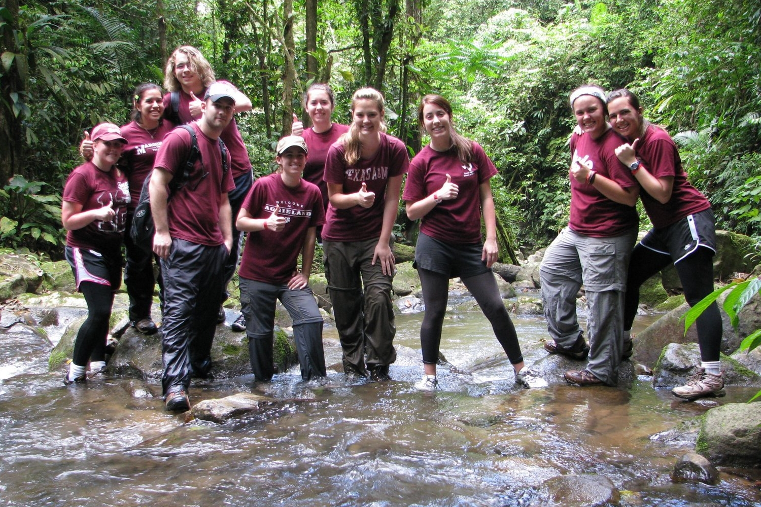 Students posing for a photo in a river in Costa Rica